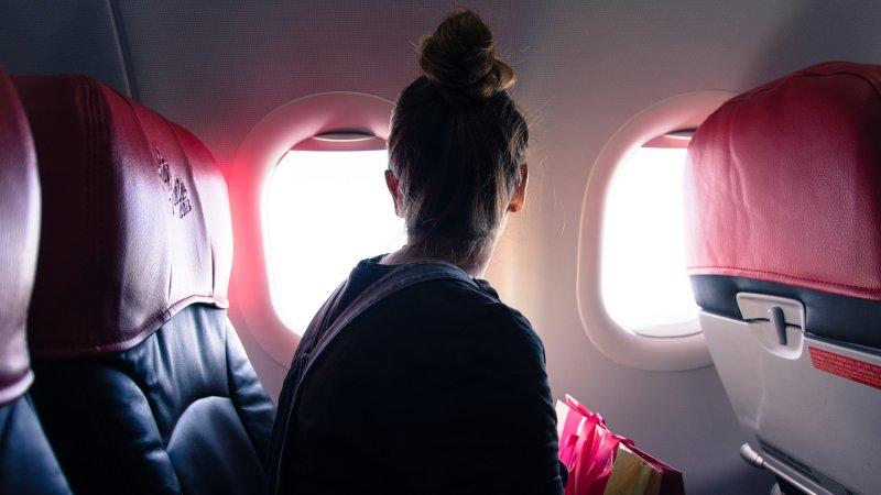 Mujer mirando por la ventana del avión